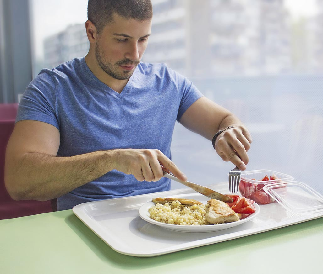 Young man sitting at the table at cafe, eating chicken lunch