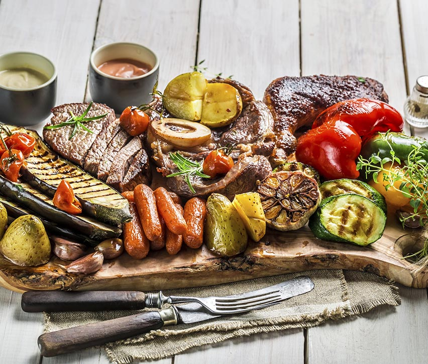 Grilled vegetables and steak with salt on white table.